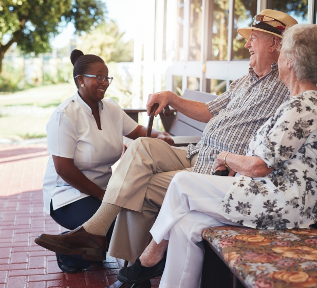 A nurse crouches to talk with an elderly couple on a bench
