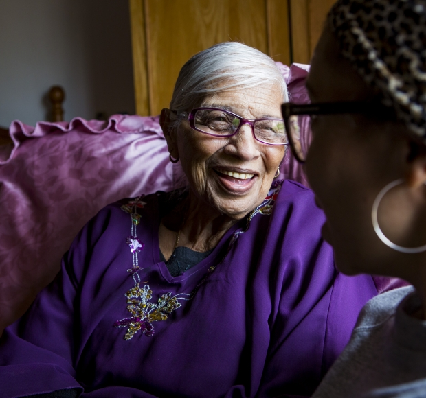 Elderly African-american woman smiling and talking with another woman